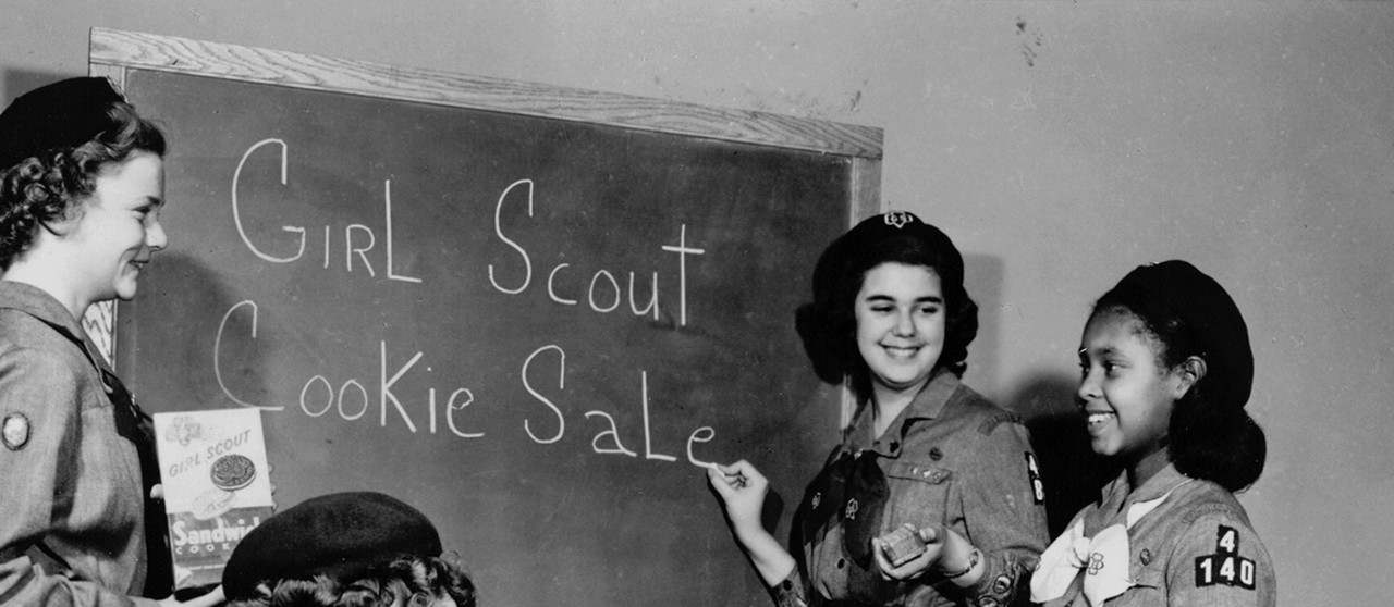 Girl Scouts at blackboard planning a Girl Scout Cookie Sale